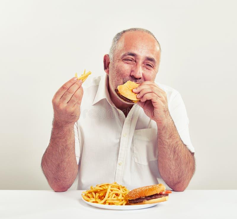 Ddle-åldras man som äter hamburgaren royaltyfri fotografi
