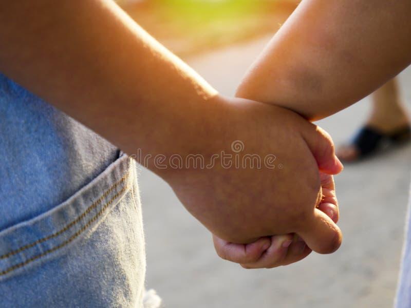 De äldre syster- och systerhållhänderna som tillsammans går, två barn som går handen - i - hand arkivfoto