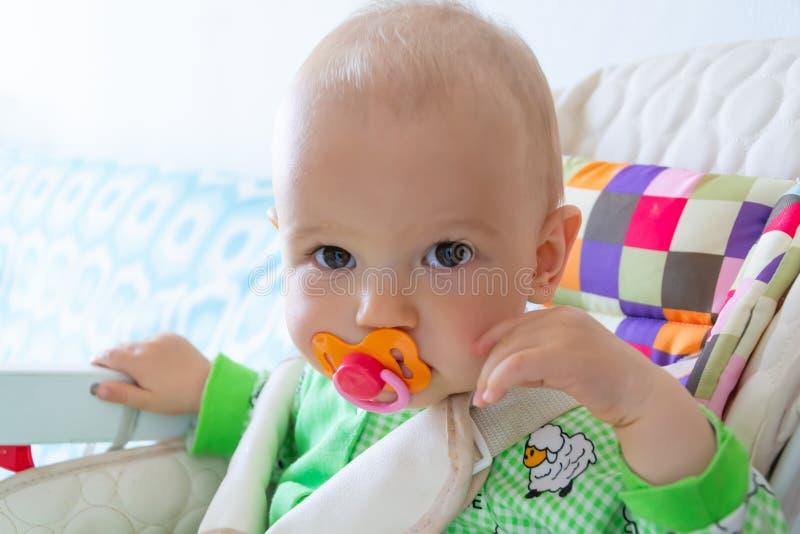 De één éénjarigebaby knaagt aan/zuigt op een rubberuitsteeksel omdat zijn tanden worden gesneden Weinig vrolijke jongen in een li stock afbeelding