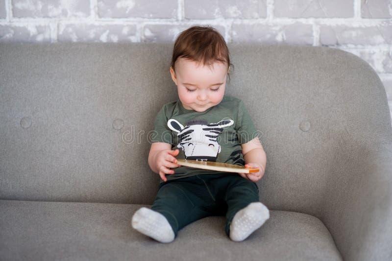 De éénjarige jongen zit op een grijze bank met een boek stock foto