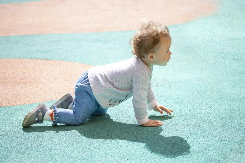 A1 de éénjarigenbaby kruipt rond de speelplaats Het jonge geitje is gekleed in jeans, sweaters en denimlaarzen stock afbeeldingen