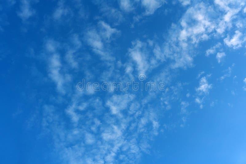 De éénmalige blauwe pluizige wolken haalden volledig al hemel over het overzees aan de zon niet nog zichtbaar, het achter de hori stock afbeelding