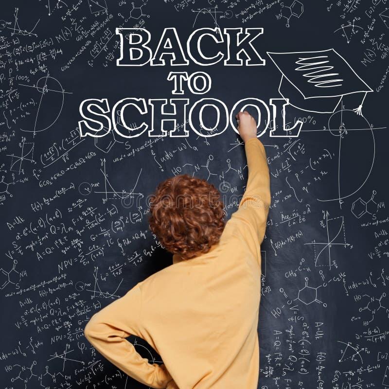 De ?hildjongen schrijft op het bord met krijt terug naar school stock foto's