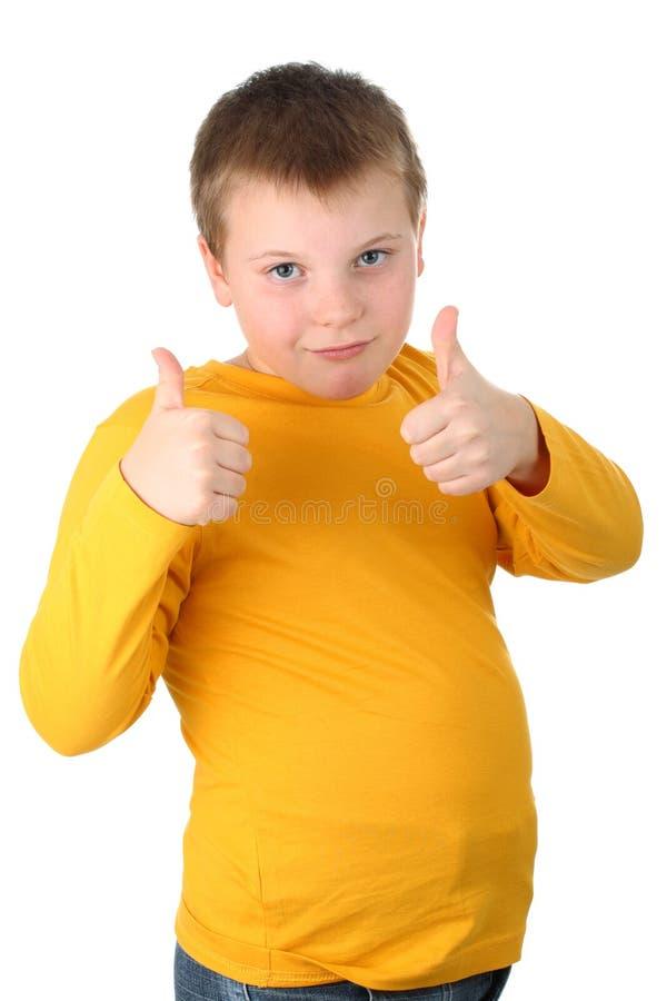 de 10 éénjarigenjongen die duimen toont isoleert omhoog op wit royalty-vrije stock afbeelding