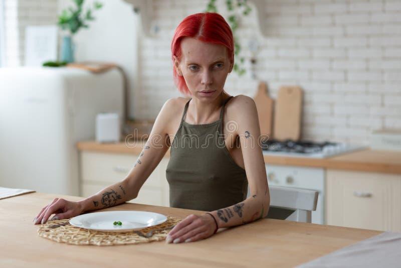 De aan anorexie lijdende vrouw die vreselijk hebben kijkt zitting in de keuken royalty-vrije stock afbeeldingen