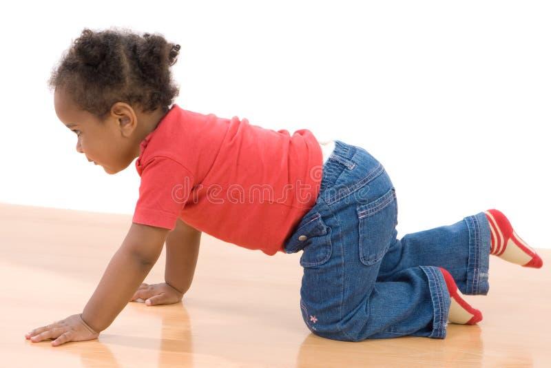 De aanbiddelijke Afrikaanse baby kruipt stock foto