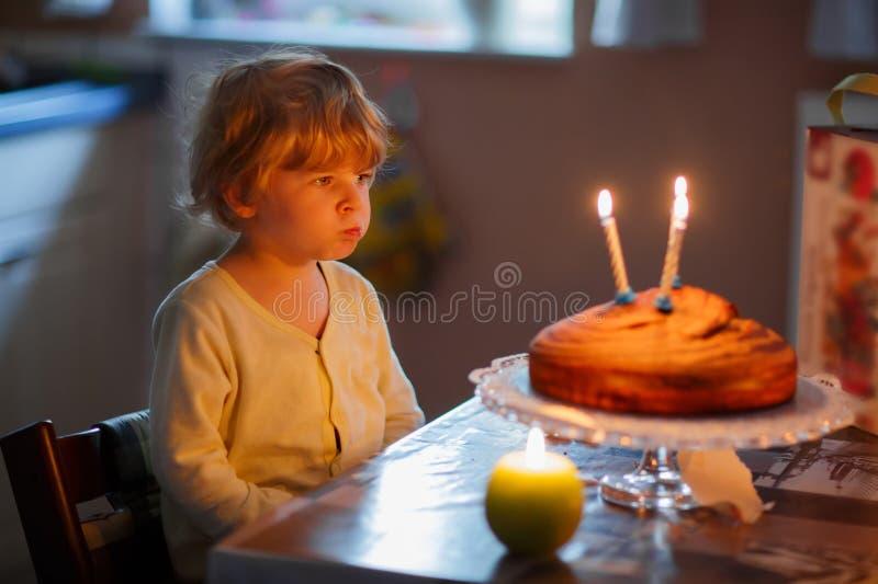 De aanbiddelijke driejarige jong geitjejongen het vieren verjaardag en het blazen kan royalty-vrije stock foto
