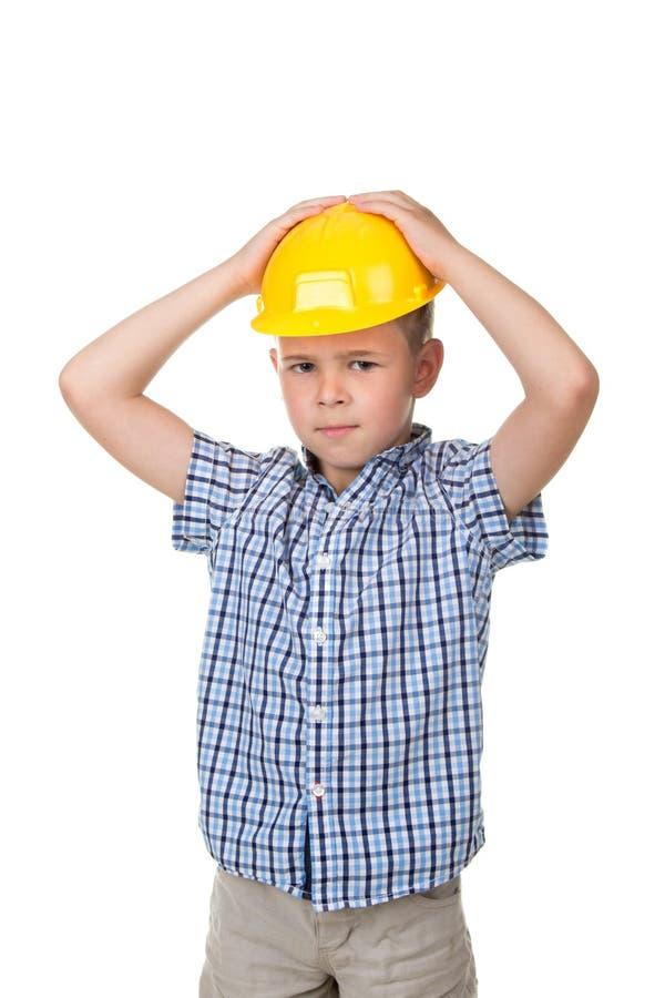 De aanbiddelijke ernstige toekomstige bouwer in gele die helm en blauw checkred overhemd, op witte achtergrond wordt geïsoleerd royalty-vrije stock afbeelding