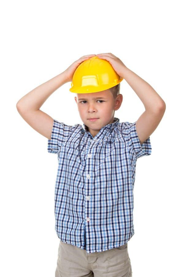 De aanbiddelijke ernstige toekomstige bouwer in gele die helm en blauw checkred overhemd, op witte achtergrond wordt geïsoleerd royalty-vrije stock foto