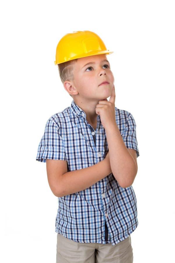 De aanbiddelijke ernstige toekomstige bouwer in gele helm en blauw checkred overhemd, heeft een goed die idee, op witte achtergro royalty-vrije stock afbeeldingen