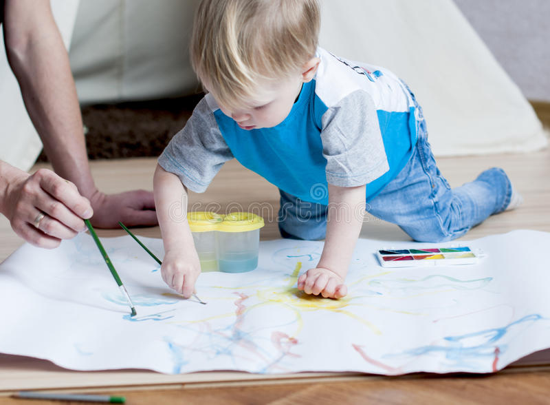 De aanbiddelijke kleine jongen probeert om met waterverf te schilderen stock fotografie