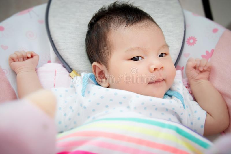 De aanbiddelijke leuke Aziatische baby bepaalt voor slaap op bed bij bedtijd stock afbeelding
