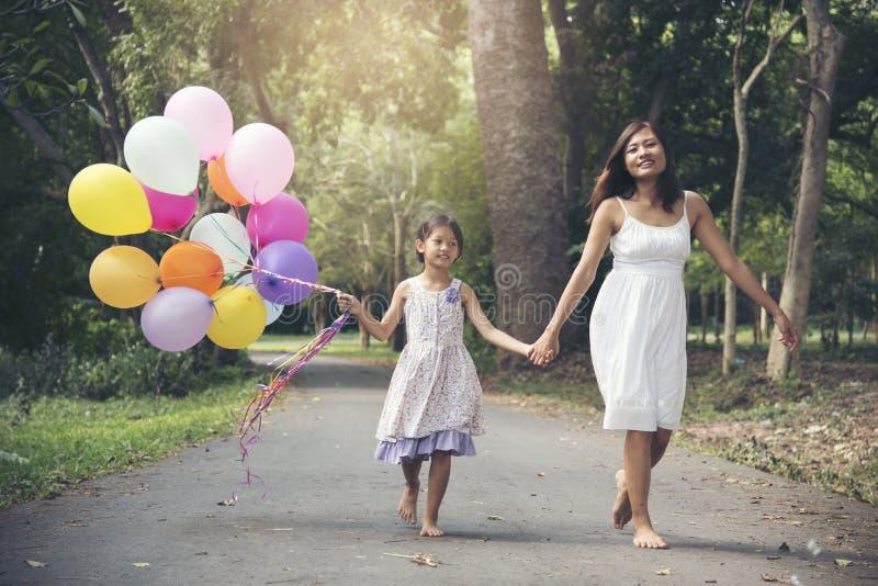 De aanbiddelijke leuke ballons van de meisjesholding met moeder die op de weg in het park lopen stock foto