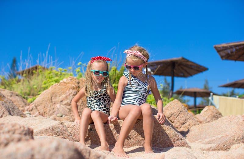 De aanbiddelijke leuke meisjes hebben pret op wit strand tijdens stock foto's