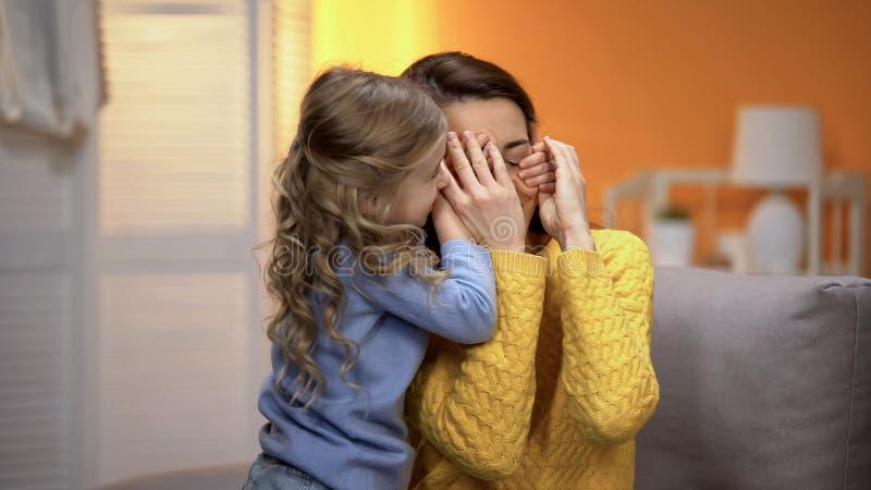 De aanbiddelijke ogen van meisje sluitende moeders met handen, gelukkige familieogenblikken stock fotografie