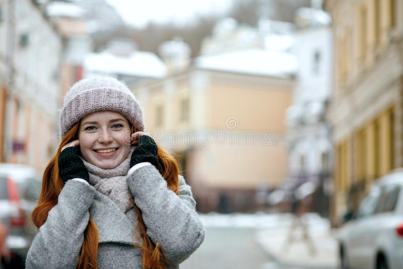 De aanbiddelijke rode haired vrouw die warme de winterkleren dragen die lopen royalty-vrije stock fotografie