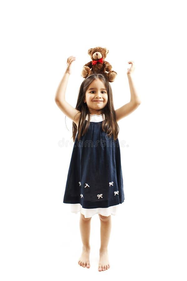 De aanbiddelijke teddybeer van de meisjeholding op hoofd royalty-vrije stock foto's