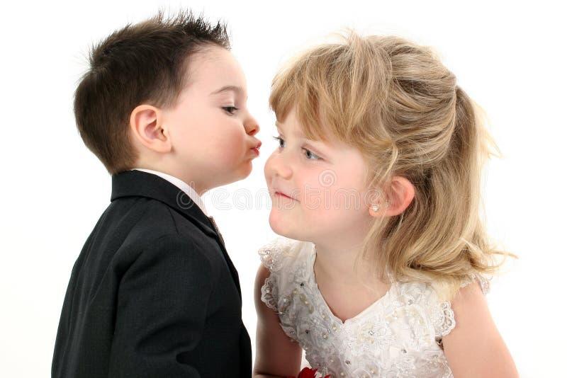 De aanbiddelijke tot Getotene Jongen van Twee Éénjarigen geeft Zijn Meisje een Kus royalty-vrije stock afbeeldingen