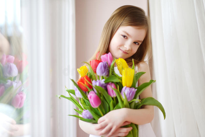De aanbiddelijke tulpen van de meisjeholding door het venster royalty-vrije stock foto's