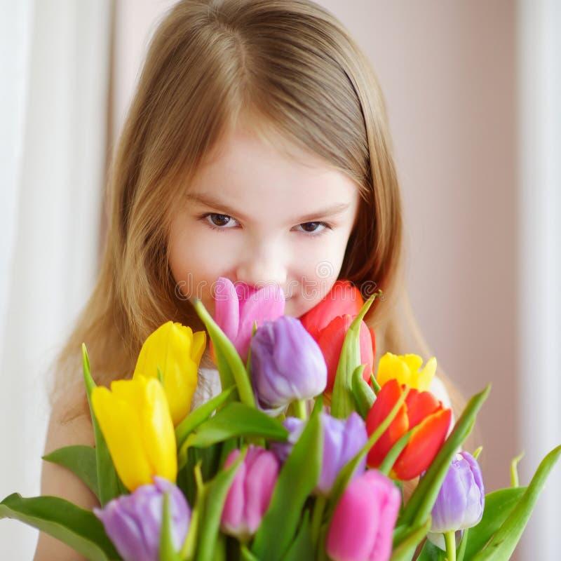 De aanbiddelijke tulpen van de meisjeholding door het venster royalty-vrije stock fotografie