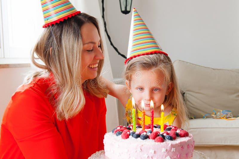 De aanbiddelijke vier van het oude Europese blondejaar meisje maakt een wens alvorens de kaarsen op een verjaardag uit te blazen  stock foto's