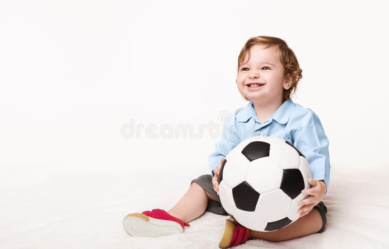De aanbiddelijke zitting van de babyjongen met voetbalbal stock foto