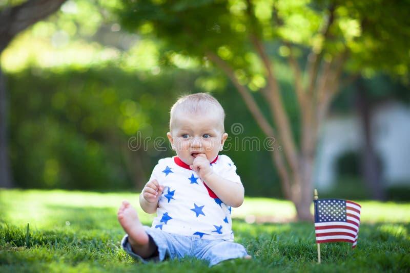 De aanbiddelijke zitting van de babyjongen op een gazon met Amerikaanse vlag stock afbeeldingen