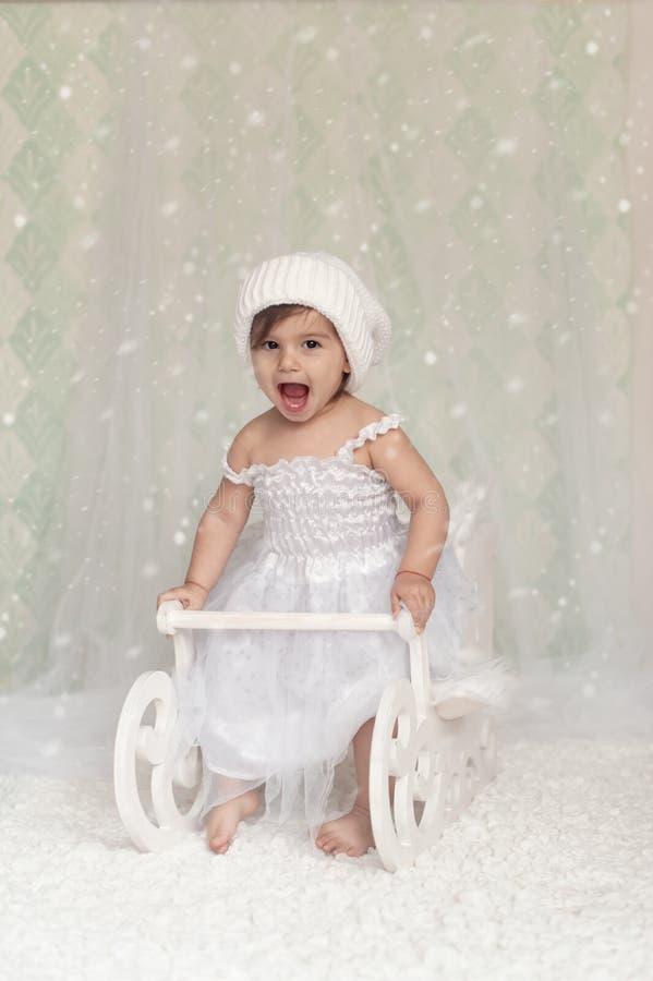 De aanbiddelijke zitting van het babymeisje in een houten ar van de Kerstmissneeuw, st royalty-vrije stock afbeelding