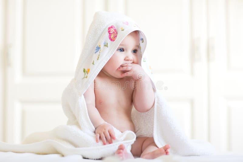De aanbiddelijke zitting van het babymeisje onder een handdoek met een kap na bad stock fotografie