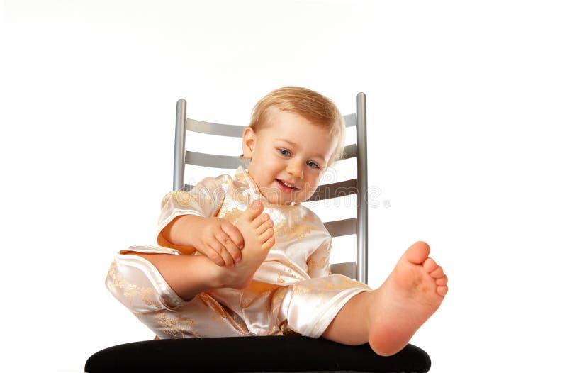 De aanbiddelijke zitting van het babymeisje op een stoel stock afbeelding