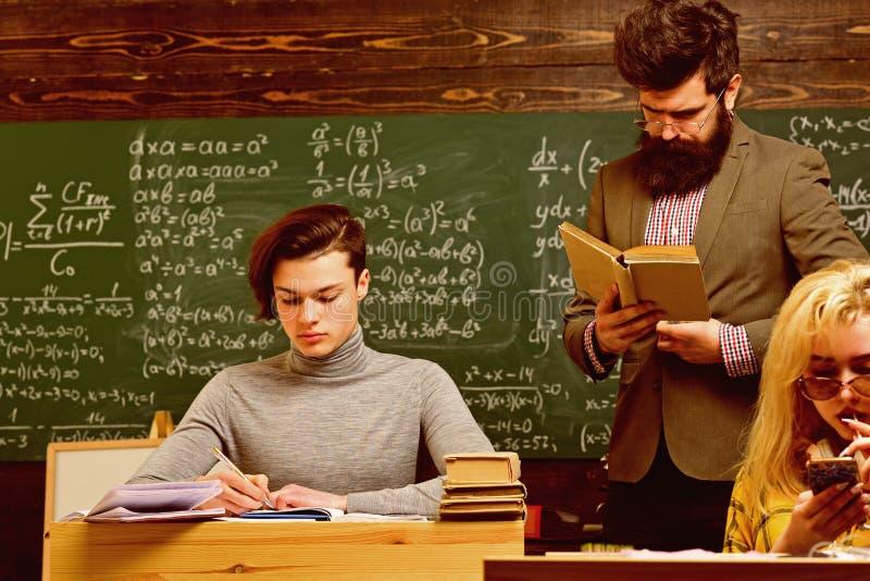 De aandachtige studenten die iets in hun nota schrijven vult terwijl het zitten bij bureaus in het klaslokaal op De studenten zij royalty-vrije stock afbeeldingen