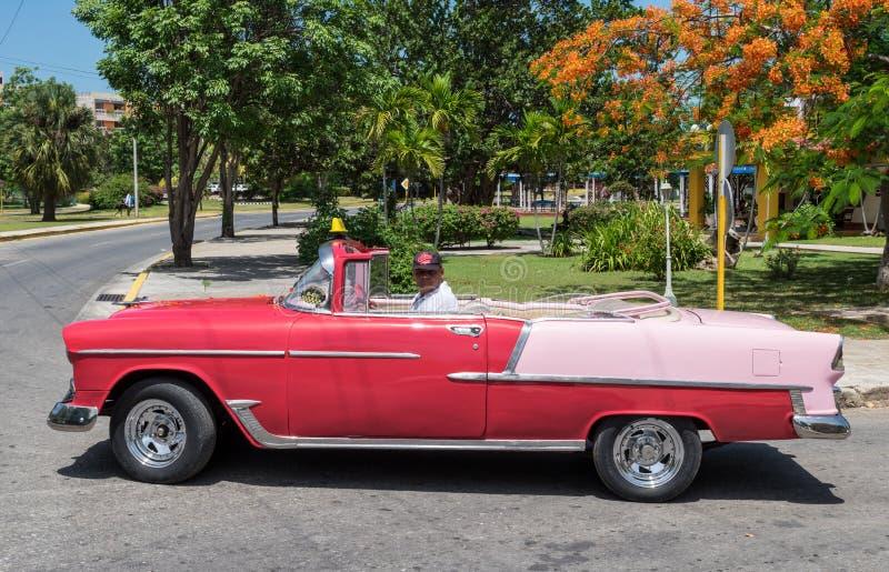 De aandrijving van Cubanen in uw rode Amerikaanse Oldtimer in Varadero stock fotografie