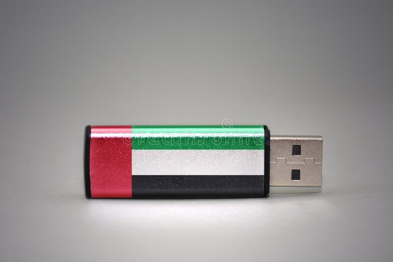 De aandrijving van de Usbflits met de nationale vlag van verenigde Arabische emiraten op grijze achtergrond stock fotografie
