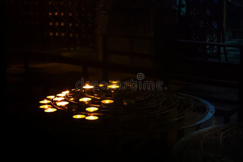 De aangestoken die omhoog kaarsen door gebeden in de duisternis van een kerkruimte in Notre Dame Cathedral, Parijs worden bevonde royalty-vrije stock foto's