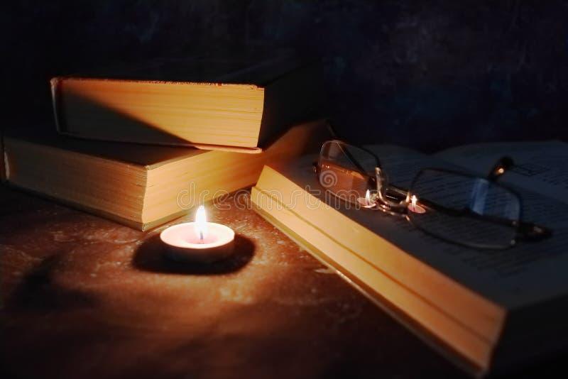 De aangestoken kaarsen in het vertrouwelijke plaatsen, oude boeken, vergeelden van tijd tot tijd, glazen in een gebreide gele dra royalty-vrije stock foto's