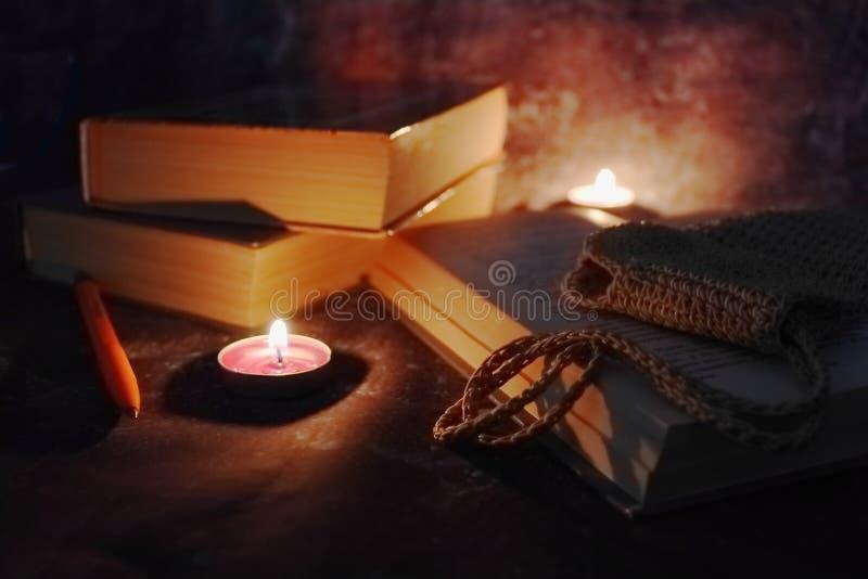 De aangestoken kaarsen in het vertrouwelijke plaatsen, oude boeken, vergeelden van tijd tot tijd, glazen in een gebreide gele dra stock afbeeldingen