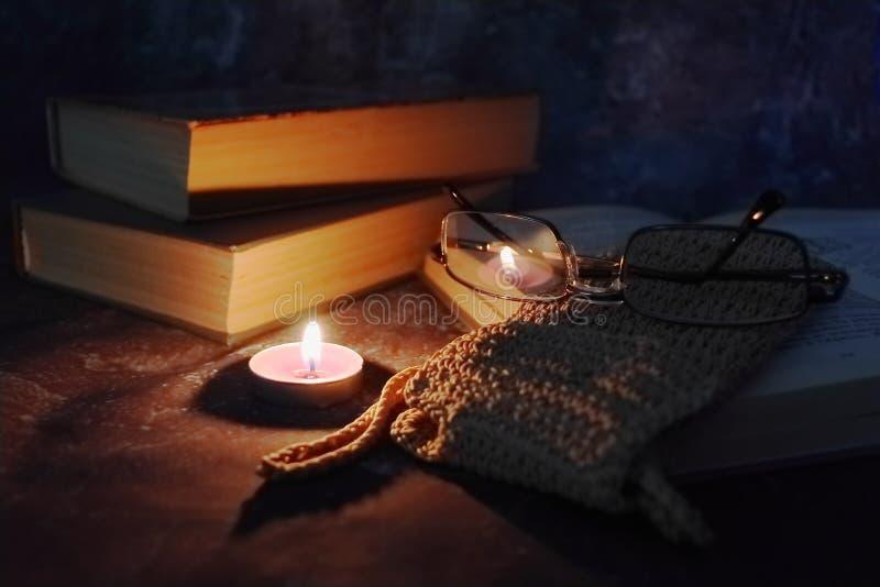 De aangestoken kaarsen in het vertrouwelijke plaatsen, oude boeken, vergeelden van tijd tot tijd, glazen in een gebreide gele dra stock foto