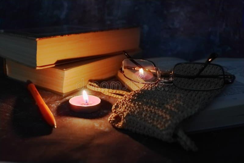 De aangestoken kaarsen in het vertrouwelijke plaatsen, oude boeken, vergeelden van tijd tot tijd, glazen in een gebreide gele dra royalty-vrije stock afbeeldingen