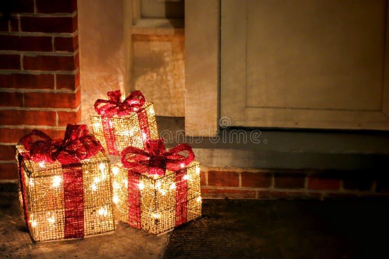 De aangestoken Verfraaide Dozen van de Giften van Kerstmis bij Deuropening royalty-vrije stock foto