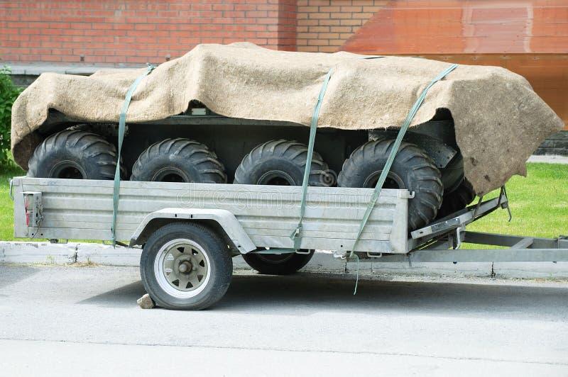 De aanhangwagen wordt geladen met automobiele banden en met een doek behandeld Het is in de straat in de zomer royalty-vrije stock foto's