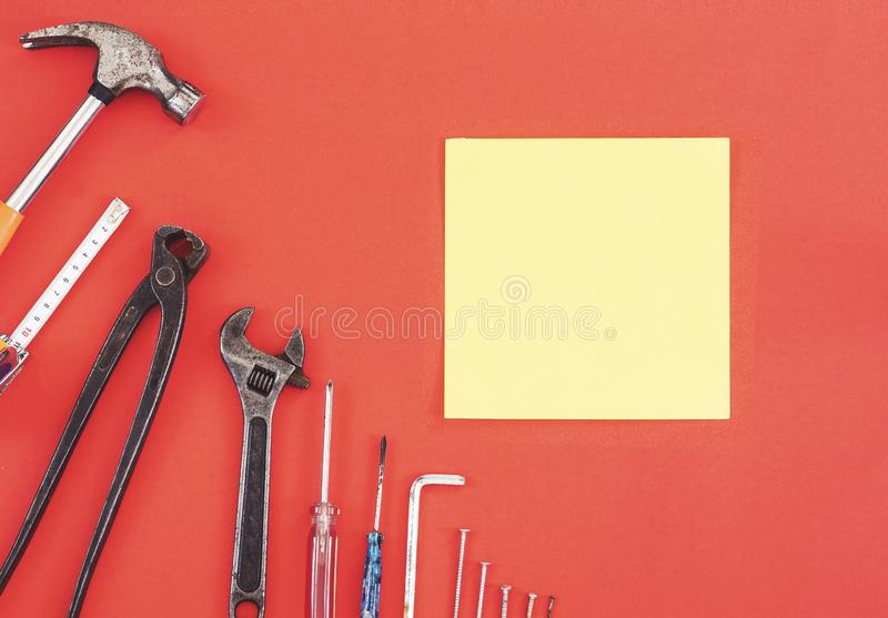 De aannemershulpmiddelen van de moersleutelingenieur op een denimarbeiders, de rode achtergrond van A met de hulpmiddelen van de  stock foto's