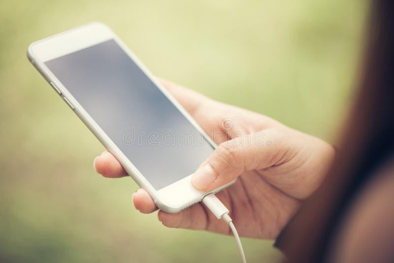 De aanraking van de close-uphand op het telefoon mobiele lege zwarte scherm openluchtlevensstijlconcept op onscherpe aardachtergr stock afbeelding