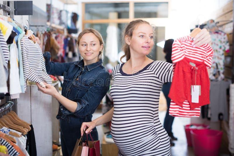 De aanstaande moeder in gestreepte uniformjas kiest kleren voor meisje stock foto