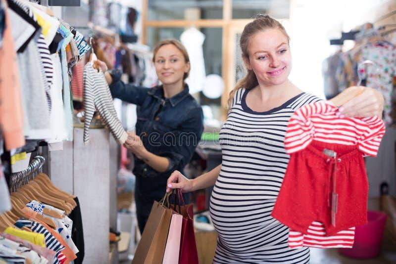 De aanstaande moeder in gestreepte uniformjas kiest kleren voor meisje royalty-vrije stock afbeelding