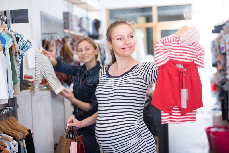 De aanstaande moeder in gestreepte uniformjas kiest kleren voor meisje stock afbeeldingen