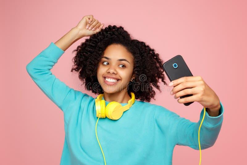 De aantrekkelijke Afrikaanse Amerikaanse jonge vrouw met heldere glimlach gekleed in vrijetijdskleding neemt beeld over met smart stock foto's