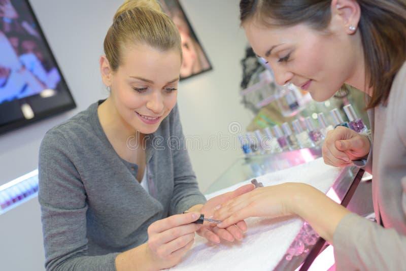 De aantrekkelijke arbeider die van de spijkersalon manicurestamgast geven royalty-vrije stock afbeeldingen