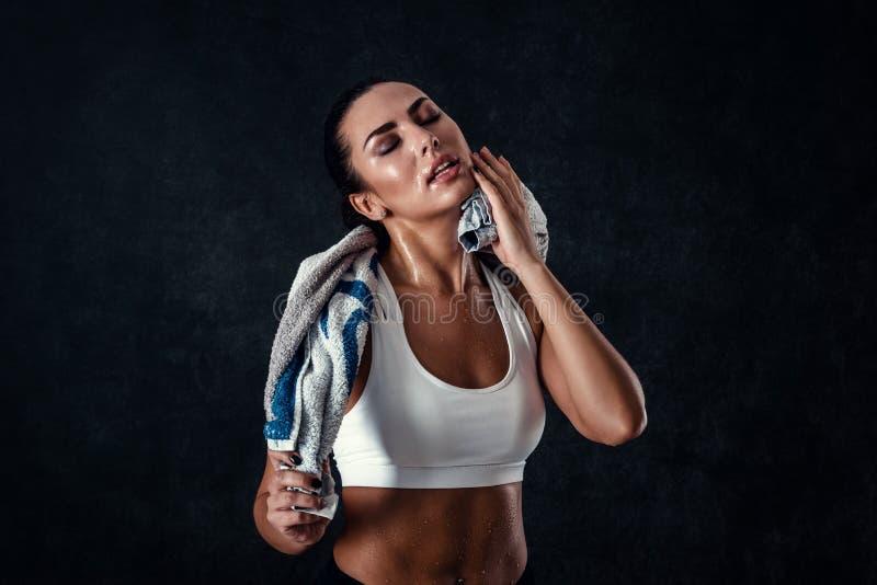 De aantrekkelijke atletische jonge vrouw met perfect lichaam die sportkleding dragen stelt met een handdoek tegen zwarte achtergr royalty-vrije stock fotografie