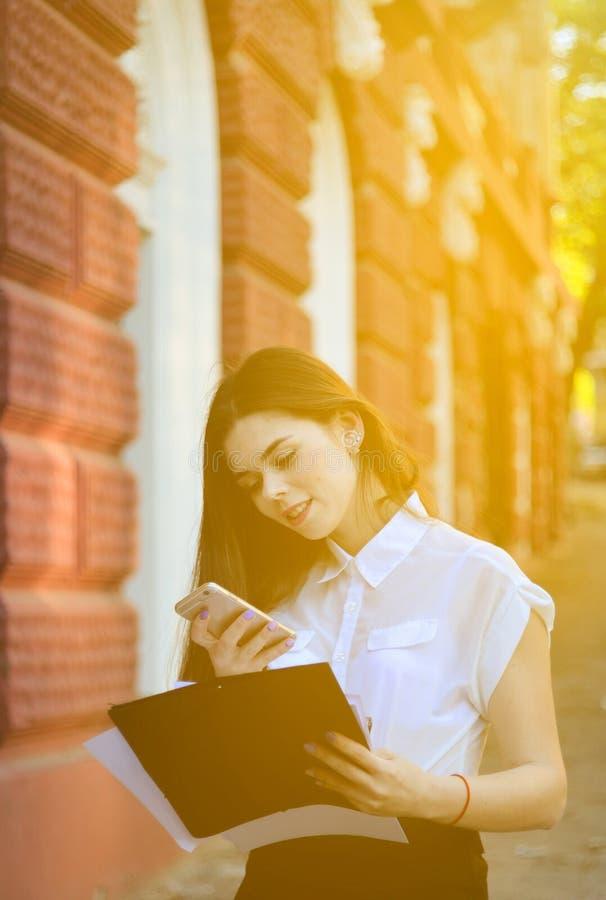 De aantrekkelijke bedrijfsvrouw glimlacht en gebruikt een smartphone het het werk proces Portret van een jonge donkerbruine vrouw stock afbeelding