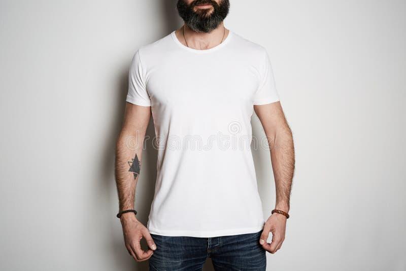 De aantrekkelijke brutale getatoeeerde gebaarde kerel stelt in jeans en leeg grijs de zomerkatoen van de t-shirtpremie, op wit royalty-vrije stock afbeelding